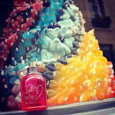 Joli visuel du parfum Amor Amor devant une montagne de bonbons multicolores façon pièce montée.