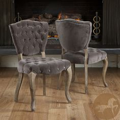 Impress guests at the dinner table by seating them in these sturdy and attractive tufted fabric dining chairs. This set of two chairs features a thickly padded seat and back and a wooden frame. The chair's weathered legs have carved details.