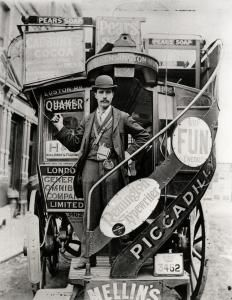 Unknown photographer, 1895-1905 London General Omnibus Corporation horse bus conductor in bowler hat and long jacket standing on the boarding platform of the bus...