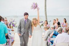 The bride lifts her purple bouquet overhead during this beach wedding recessional.