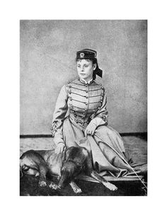 """Army Letters from an Officer's Wife, 1871-1888."" Frontispiece of Frances M. A. Roe and Hal, her faithful greyhound companion. What is remarkable about the portrait is the altered dress made from Fayette Roe's West Cadet coatee with decorative braid and brass buttons. The forage cap -a small brimmed cap with a squashed crown, is adorned with the United States Military Academy insignia. A riding crop in her left hand details her expert equestrians"