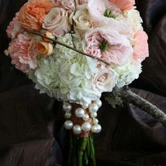 Peach ranunculus and roses along with pink garden roses and curly willow perfectly accented white hydrangea in his elegant bridal bouquet. The piece was finished with a rust satin detail for contrast Along with great pearly baubles for a more modern take of a bridal classic. Simplyrosesflorist.com original.