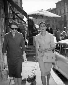 The actress Audrey Hepburn photographed with Mr. Famous and her mother, the Baroness Ella Van Heemstra, in the Piazza di Spagna in Rome (Italy), on October 16, 1959. Audrey was wearing: Ensemble: Givenchy (of wool with a coarse weft in the tissue like a plaid, short coat accompanied by a belt lined in the same tissue and a sleeveless dress, of his collection for the Spring of 1958). Handbag: Hermès (of leather in the ecru color, created exclusively at Audrey's request in 1956). Audrey…