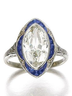 An Edwardian sapphire and diamond ring, Circa 1910. Centring on a navette-shaped…