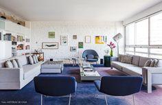 Sala de estar minimalista tem móveis em cores neutras, parede de tijolo branca e estante que toma toda a extensão da sala.