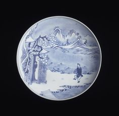 A porcelain shallow dish with rounded sides which slope inwards at the rim, and stands on a low straight foot ring. Decorated in underglaze blue with a snowscape showing a man, wearing a short robe and trousers, carrying a hu-shaped wine jar and running towards another man half-appearing at the door of a pavillion at the edge of a river. The outside covered with a blue-white matte glaze. The base with a six-character mark.