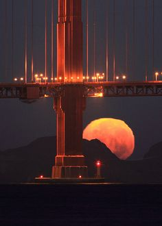 ∆ Moon Magick... the full moon setting behind the base of the south tower of the Golden Gate Bridge.