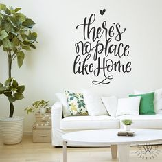 """""""There's No Place Like Home"""" written in black vinyl on white wall above a white couch with green and white pillows. The vinyl quote wall is written in beautiful handwritten calligraphy and there is a small heart at the very top of the quote. Vinyl Wall Quotes, Vinyl Wall Stickers, Quote Wall, Bathroom Wall Quotes, Vinyl Sayings, Bedroom Quotes, White Couches, White Pillows, Yellow Walls"""