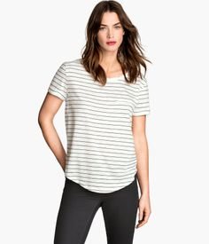 Top in soft slub jersey with a slightly twisted neckline, one breast pocket, short sleeves with sewn-in turn-ups, and a rounded hem.