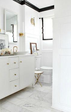 Black and white bathroom with gold faucets and fixtures designed by Kristin Cadwallader.