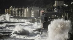 Waves crash over the main Exeter to Plymouth railway line that has been closed due to parts of it being washed away by the sea on Feb. 8, 20...
