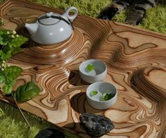 Topographic Tea Table  Make teatime memorable with the topographic tea table. Layers of laminated plywood accentuate the undulating form through alternating dark and light seams to create a serene landscape with carved niches and plateaus to accommodate the tea set.  $1700.00  Check It Out  Awesome Sht You Can Buy