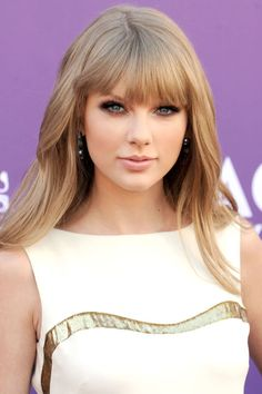 Swift goes for a mature look with blunt bangs and soft waves combined with her signature smoky eye and nude lip.
