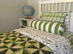 child's bed, green textiles from IKEA and Target, handmade quilt, vintage globe, bolster pillow
