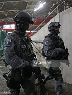 Two British Counter Terrorist Specialist Firearms Officers (CTSFO) carry their guns as they patrol inside Wembley Stadium ahead of the friendly football match between England and France at Wembley Stadium in west London on November 17 2015. [451x594]