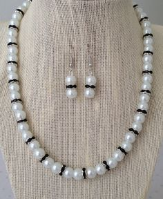 A stunning black and white glass pearl rhinestone necklace and earring set. This lovely jewelry set is designed with white glass pearls and black rhinestone rondelle metal beads. Necklace available with a silver lobster clasp w/ 2 inch extender chain or a silver toggle clasp; (you