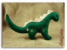 Dinossauro tipo dragon, patas articuladas. Confeccionada em feltro. Fibra siliconada. Botão. Personalizada. R$ 22,50