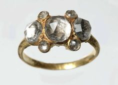 Ring made of gold with traces of black enamel, has a bezel set with seven mirror-backed faceted glass pastes. These so-called 'Vauxhall pastes' were flat-backed glass paste gems whose faceted surface was reflected in the mirrored back giving an illusion of great depth.  Production date - 1600-1699
