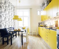 How cool is this narrow galley kitchen made by the bright yellow cabinets, playing off the toile covered accent wall?