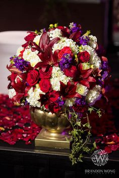 Burgundy, red, purple and white flowers in a statuesque gold vase