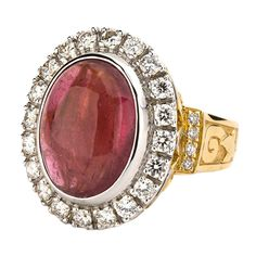 Primavera 8.40 Carat Rubellite Tourmaline Cabochon Diamond Gold Ring. This mesmerizing cocktail ring, centers on an oval-shaped cabochon cut Rubellite Tourmaline stone weighing 8.40 carats, in a 18K Yellow Gold Shank, 18K White Gold top setting. Surrounding the Rubellite Tourmaline stone is a diamond border comprised of 20 sparkling diamonds (1.20 carats), which frame the center stone perfectly, creating a stunning halo. 21st century
