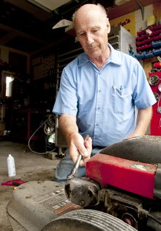 """Merlin Humpherys changes a spark plug on a brush trimmer in the garage of his Smithfield, Utah, home. Humpherys was featured in The Herald Journal's """"Good Neighbor"""" series. (Photo by John Zsiray)"""