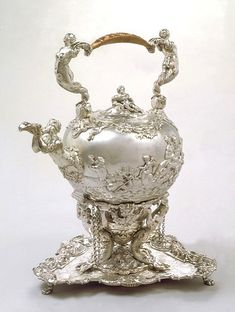 Kettle and Stand, Charles Frederic Kandler, 1730-2. An early Rococo decorative style. The stand is made up of three mermen, and the handle is formed of mermaids, while the spout is formed of a triton, blowing a conch horn. Each side of the kettle depicts the story of the sea deities Neptune and Amphitrite, the lamp-stand is decorated with marine creatures, and the engraved armorials on the salver are flanked by further depictions of marine gods and goddesses.