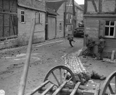 American soldiers try to cross the street with the protection of Sherman tanks while under fire from a sniper. KIA was Off Robert hardy Dunne from Texas from 44th AIB  B Company 4th April 1945.  On the corner of Heyerode stress and Sperlingberg st