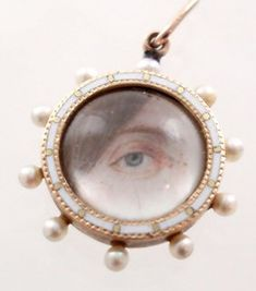 Georgian eye miniature brooch, circa 1830, round lover's eye miniature of a female blue eye with hair painted on ivory under rock crystal. Gold frame is enameled in white with natural pearls set in a wheel formation.