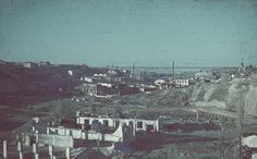 """Damaged buildings in southern Stalingrad, Russia, 23 Sep 1942.  Looking downstream in Tsaritsa Gorge. The Volga in the distance. In the shade at left is a bridge. Beyond the bluff at right is the """"German Castle"""" by Pushkinskaya Street. This image is mistakenly flopped (left/right)."""