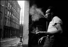 Erich Hartmann. USA. New York City. 1955. Man smoking in the streets under the Brooklyn Bridge.