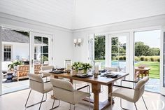 The dining room's oak table is set with Ralph Lauren Home hurricane candleholders, and the 1960s chairs from R. E. Steele Antiques are covered in a Perennials fabric | archdigest.com