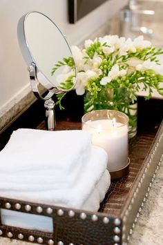 Home decorating ideas - bathroom tray styling for the countertop featuring a silver sparkly stand mirror, fresh floral arrangement, white candle and fluffy white towels all set inside a faux leather tray with nailhead trim.