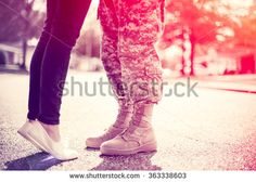 Young military couple kissing each other, homecoming concept, soft focus, cross…