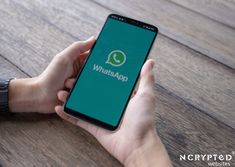 Man holding a smartphone with open whatsapp on the screen.