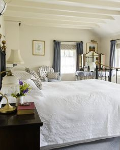 Family antiques and layers of textiles create the welcoming cottage style of the main bedroom. White bedding from The White Company and Cologne and Cotton is paired with soft blues and cream