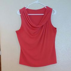 "Orange drape neck sleeveless slinky top  Lg Orange drape neck sleeveless slinky top size Lg, draping neckline criss-cross to opposite shoulder.  93% polyester 7 % spandex. Goes perfect with orange flowered pencil skirt in this closet. 29"" length shoulder to hem, 45"" bust arm pit to arm pit, 39"" waist Worthington Tops"