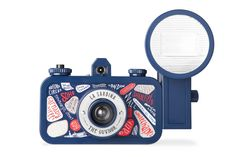 """Prepare for countless wide-angle adventures with the La Sardina & Flash """"The Guvnor"""" Edition! This camera is a celebration of the exciting city of London, home to one of the most active Lomographic communities in the world. Dressed in Union Jack colors and decorated with iconic London landmarks, this special La Sardina edition will perfectly capture your memories."""