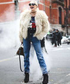 Look inverno da NYFW com calça jeans, t-shirt e casaco peludo.