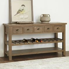 Constructed from reclaimed pine, this console table's design retains the rustic warmth of raw wood for casual appeal. Burnished metal cup pulls on the five storage drawers complement the roughhewn look, and a built-in wine rack safely stores up to twelve bottles of wine.