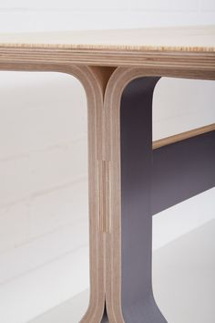A close up of the beautiful vacuum curved birch plywood table legs, on Lozi's modern and minimalistic Sea Table.