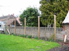 Ivy Clad: Privacy by Pleaching. Very young trees have been planted along a framework of wood posts and wires. The trunks have been cleared of any branches that are below the desired height of the hedge as well as cleared of any branches that cannot be directed into the horizontal framework.