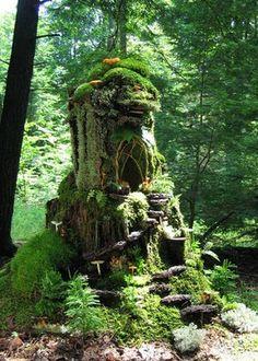 Moss, fern and tree trunk garden sculpture
