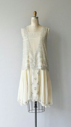 Antique 1920s ivory silk dress with stunning metallic silver beading, classic drop waisted shape and attached silk slip.