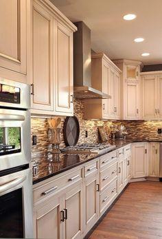 light cabinets, dark counter, oak floors, neutral tile back splash.