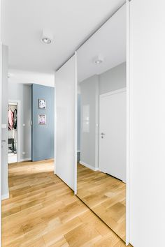 Natural wood floor with white built-in wardrobe, sliding door with mirror.