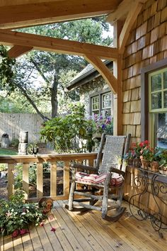Cedar shakes and a vintage hickory rocker give this porch a rustic feel. - Cabin Life Magazine