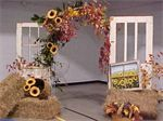 Old doors, an arch, hay, and sunflowers used at a retirement reception.