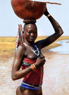 Mulher Dinka Woman vestindo um espartilho, carrega uma cabaca no Sudao do Sul. Fotografia: Carol Beckwith & Angela Fisher.