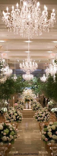Stunning Ceremony Decor. Adding trees to it brings the outdoors in and those chandelieres mantains the elegance!